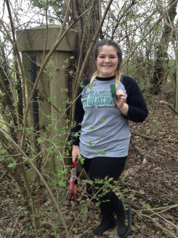"Found it! Sophomore Sydney Moore finding a hidden geocache after a long search.  ""Geocaching is so much fun, the suspense of maybe finding a cache or maybe being disappointed is one of my favorite things. My favorite caches are the ones that have stories behind them and with fun clues. I would recommend everyone try it,"" says Moore."