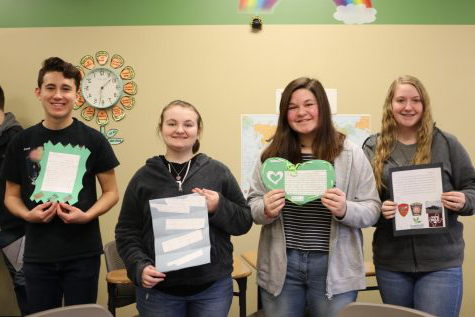 "Spanish II students  (Hannah Gillespie, Karrigan True, Caiden Scott, and Gideon Hill) hold their pen pal letters. ""I just received a letter from my pen pal, Blair, for St. Patricks Day,"" True said."