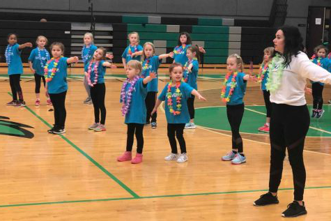 Claire Palmer teaches the elementary school kids the dance at the 2019 mini cheer camp.