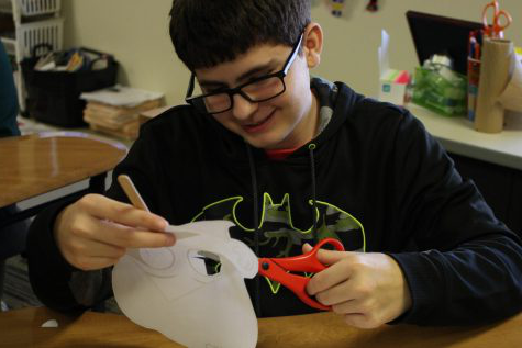 Spanish two student, Kolbee Grider, cuts out his mask that he will use for the remainder of Wooly week. Grider chose a mask from a Señor Wooly music video that his class had watched in one of their previous Wooly Wednesdays.