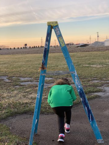 Carly Fitzpatrick walks under ladder, which is a common superstition. The superstistion of walking under a ladder came from the ancient Egyptians because they regarded the triangle as a sacred symbol of the gods and to walk through them disrespected the gods.