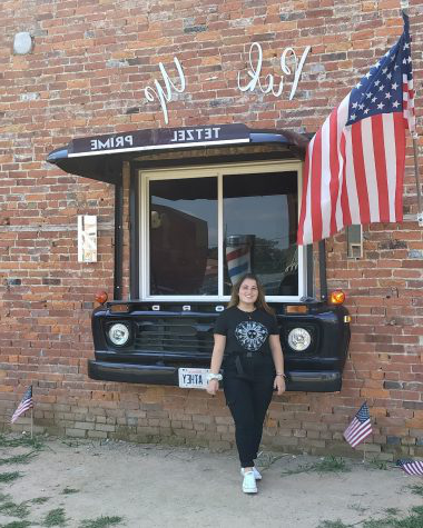Victoria Muller posing with American flag. Photo taken 通过 her host mother in Casey, Illinois.